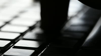 stock-footage-man-typing-on-computer-keyboard-high-contrast-backlit-with-shallow-depth-of-field